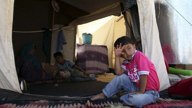 Boy outside tent in refugee camp