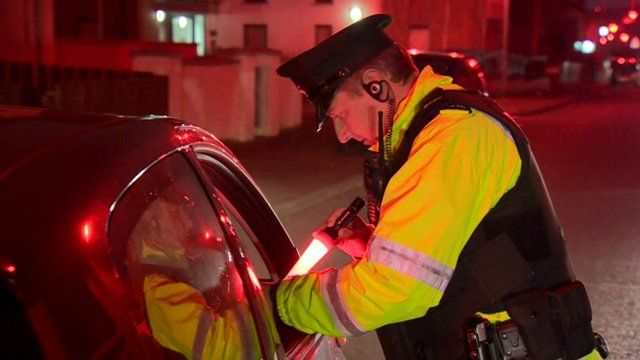 A police officer checking vehicles in Belfast