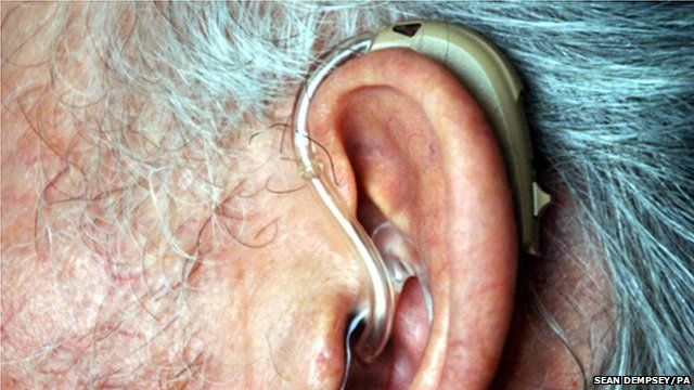 An elderly person wearing a hearing aid