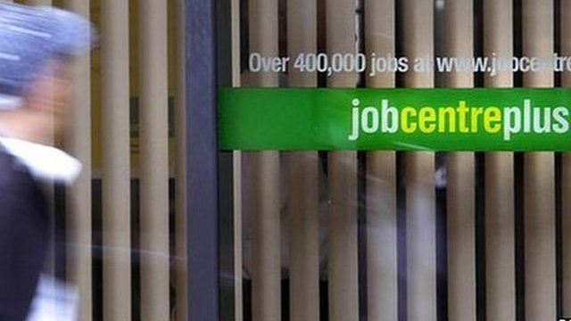 Man in front of Job Centre window