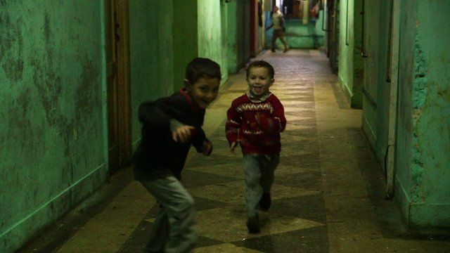 Samuel and another Roma boy play in the corridor of the derelict laboratory