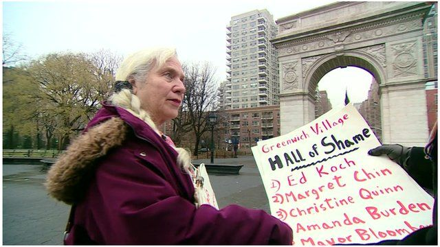 Activist holding up a poster criticising mayor Bloomberg