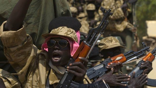 A SPLA soldier gestures as he sits in a vehicle in Juba