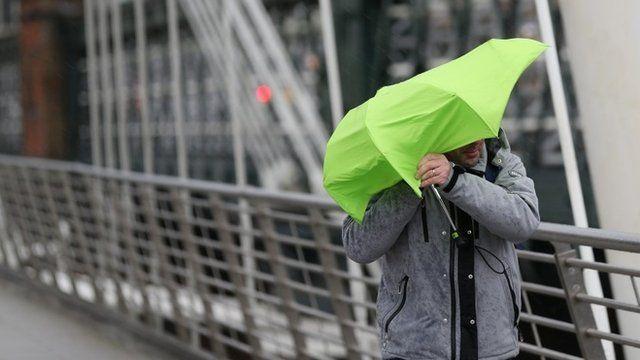 A man struggles with his umbrella