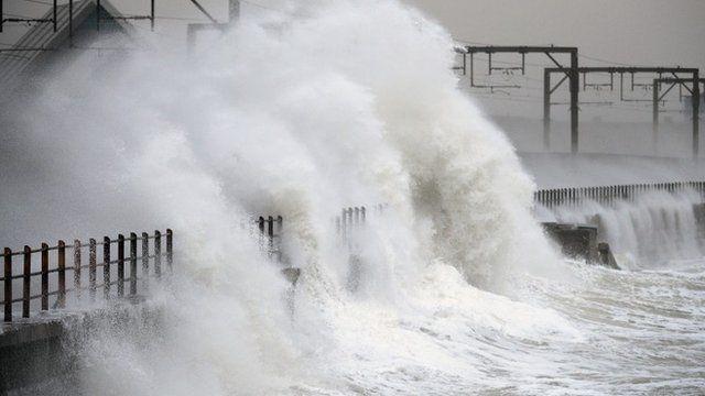 Waves crash over a wall near Saltcoats station