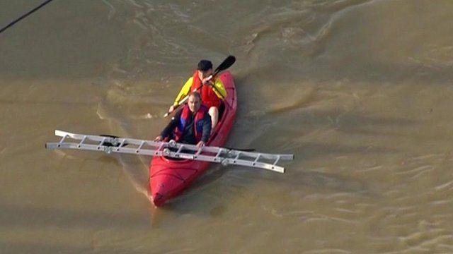 Men carrying ladder in canoe