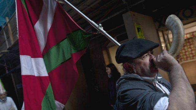 Man in traditional Basque clothing carrying Basque flag