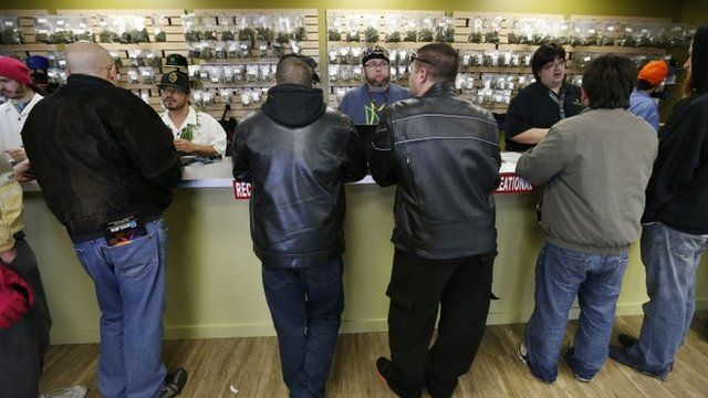 Employees help customers at the crowded sales counter inside Medicine Man marijuana retail store, which opened as a legal recreational retail outlet in Denver on Wednesday Jan. 1,