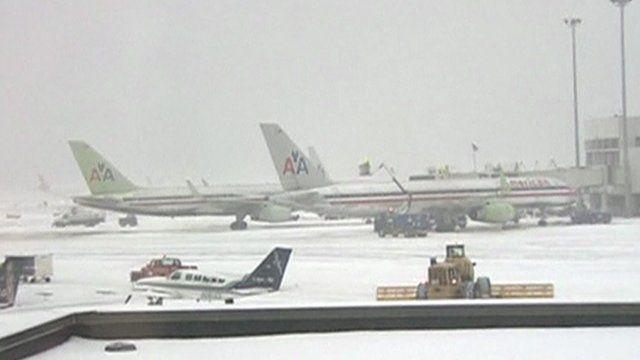 Snow plough on runway near passenger planes