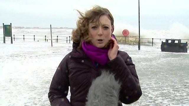 Waves crashing over promenade behind Laura Bicker