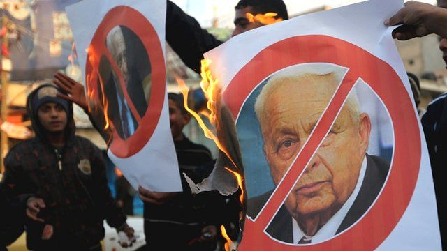 Palestinians burn a poster of former Israeli Prime Minister Ariel Sharon in the southern Gaza Strip