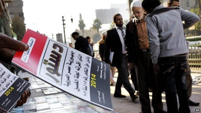 Egyptian vender sells copies of the new constitution in Cairo