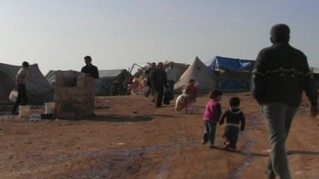 Man and children in Syrian refugee camp