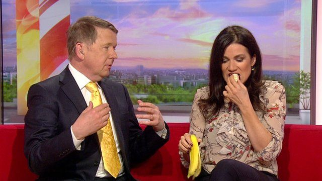 Bill Turnball looks on at Susanna Reid eating a banana