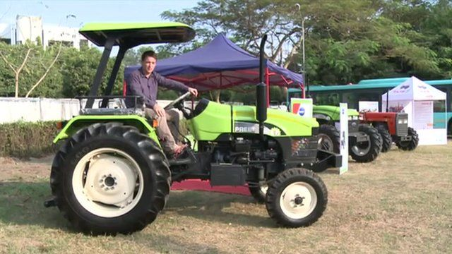 Jonah Fisher sits on a tractor at Yangon trade fair