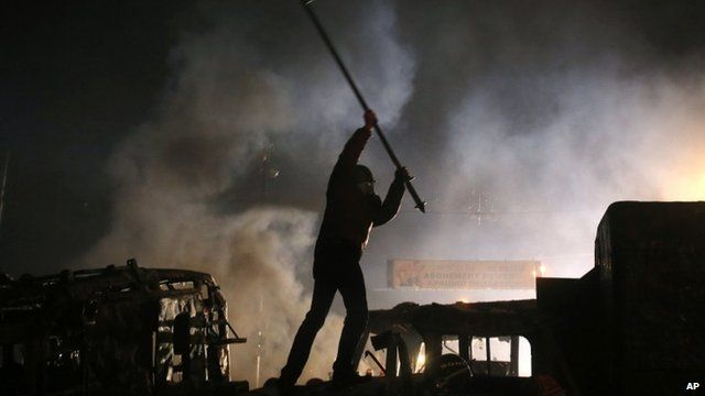 A protester stands on top of a barricade during during clashes with police in central Kiev, Ukraine