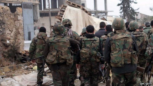 A handout picture released by the official Syrian Arab News Agency (SANA) on January 13, 2014 shows pro-government forces walking in part of the northern Syrian city of Aleppo