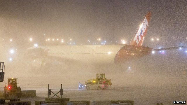 A plane shrouded by snow at JFK Airport, New York