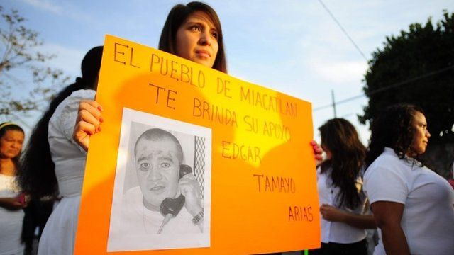 A woman in Mexico holds up a sign showing a photo of Edgar Tamayo Arias