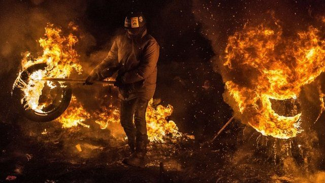 Activists of Euromaidan (the name given for Independence Square) burn tyres and warm themselves at a barricade in the centre of Kiev early on January 24, 2014
