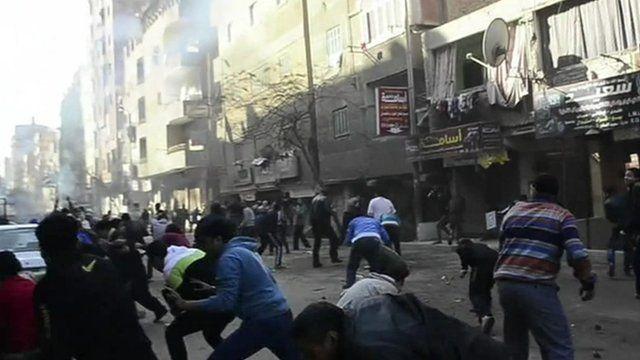 Men in street ducking as explosion rocks Cairo