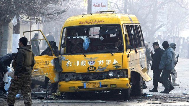 Afghan policemen inspect the wreckage of a bus hit by a suicide attack in Kabul