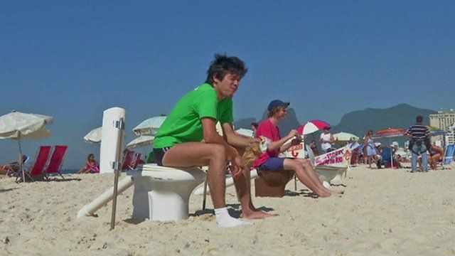 Campaigners sit on toilets on Ipanema beach