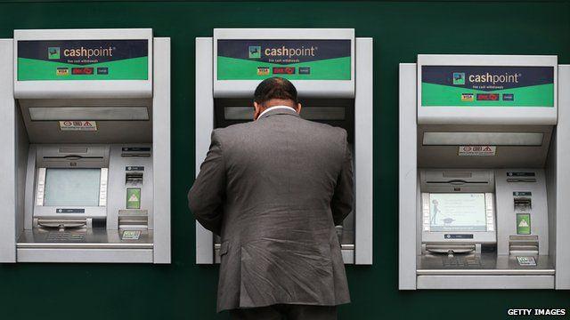 A customer uses a cash machine at Lloyds Bank branch