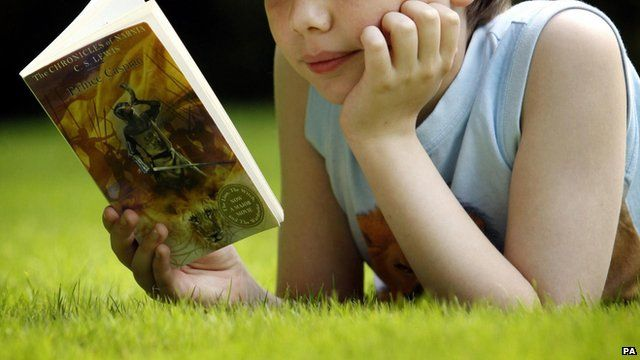A child reads a book on the grass