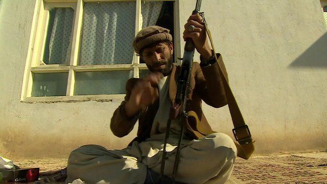 Afghan man cleaning and assembling his rifle