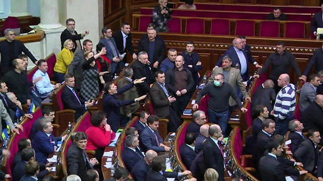 Politicians shouting and waving in parliament