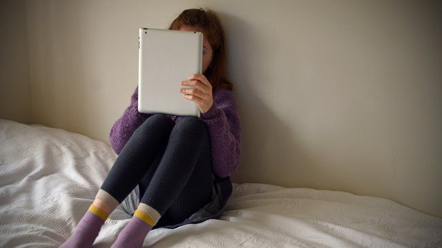 Young girl plays on a tablet