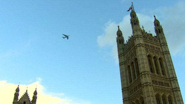 A plane flies over the House of Parliament