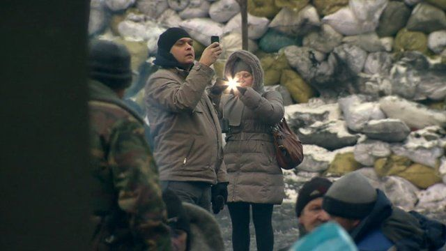 Man and woman take photo on their phones