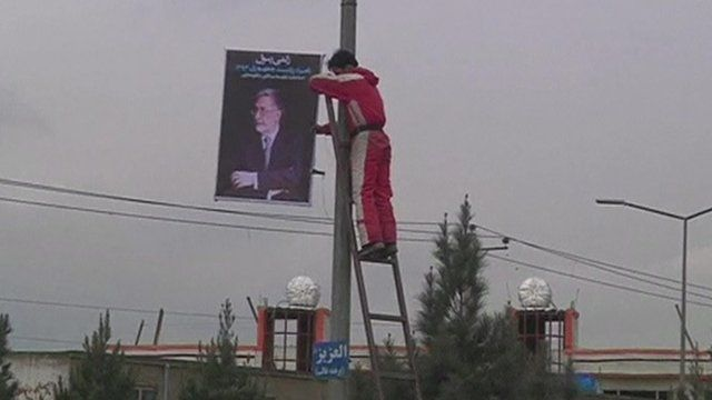 Man hanging candidate poster from lamppost