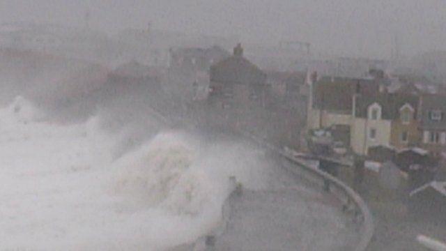 Waves crashing over the sea wall overlooking Chesil Cove, Portland, Dorset