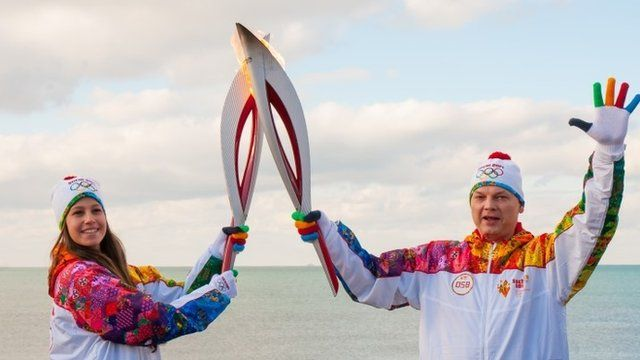 Torch bearers pose with Olympic torches during the Olympic torch relay in Lazarevskoye neighbourhood of Sochi