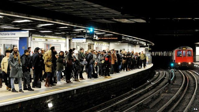 Passengers wait on the east bound platform of the District Line at Victoria Station