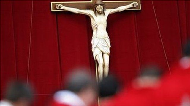 Priests stand in front of a crucifix (19 May 2013)