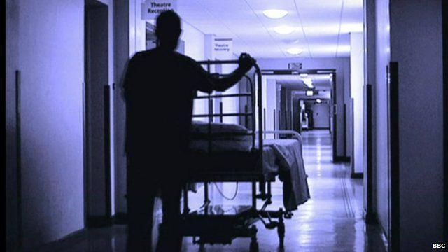 Outline of man pushing empty hospital trolley down corridor