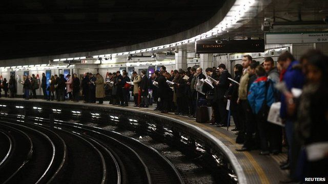 Passengers at a Tube station in the evening