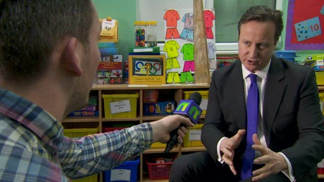 David Cameron speaking into a microphone with Martin Dougan