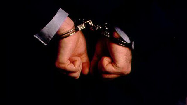 An anonymous man in handcuffs