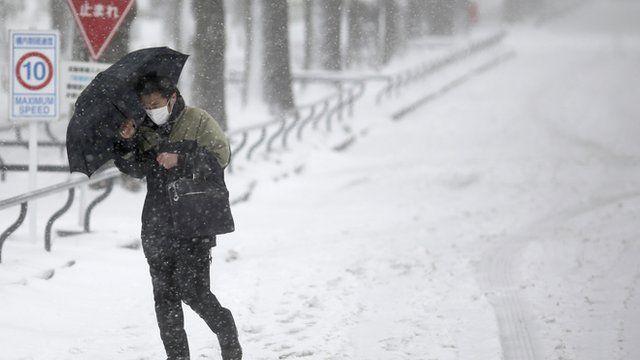 A man walks against a snowstorm on a snow-covered road in Yokohama, Japan