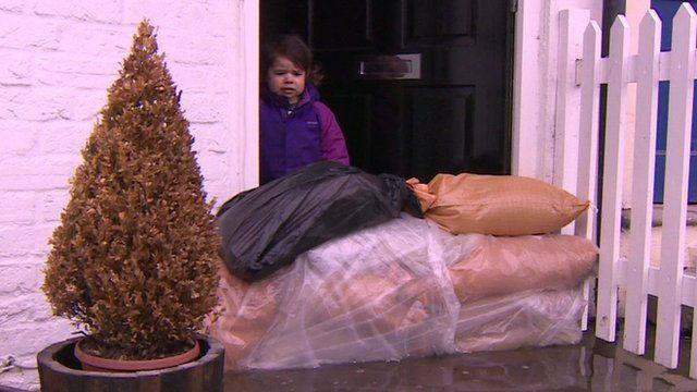 Child standing at door next to sandbags