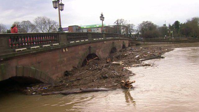 Debris and silt gathered around bridge supports in Worcester