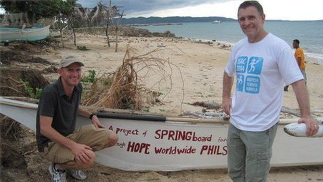 Head of British School Simon Mann and another man next to a boat.