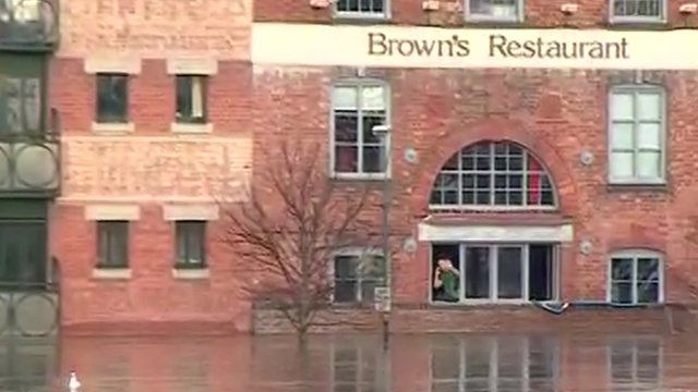 Nathan Roy Smith waving from window of flooded restaurant