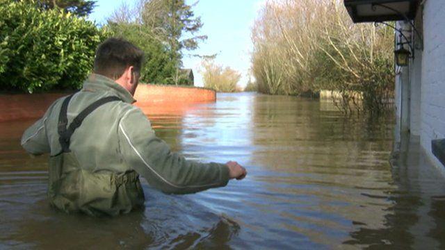 Man waist deep in water on flooded street