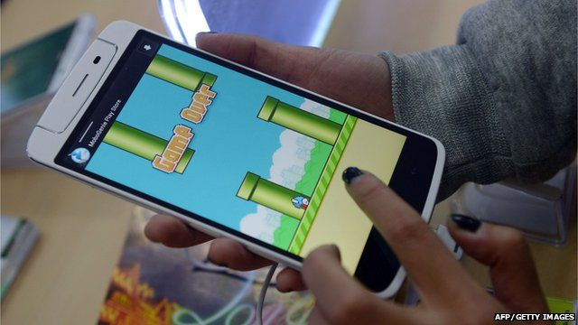 An person plays the game Flappy Bird on a smartphone